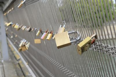 Photo of padlocks attached to a bridge.
