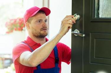Photo of a Gloucester locksmith checking that a newly installed door lock is working.